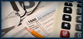 Image of different tax documents with a pencil, calculator and glasses laying over them.